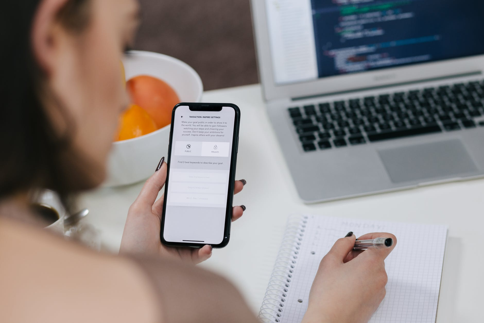 person looking at phone while writing notes