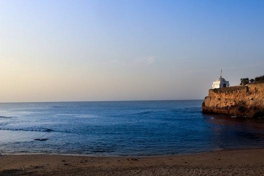 White Lighthouse Near Sea Under Blue Sky