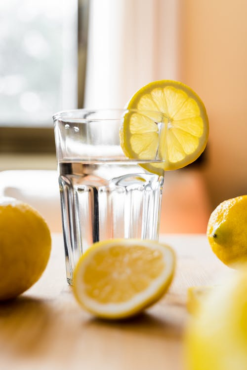 Glass of cold water with lemon placed on table