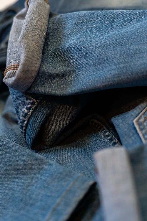 Trendy blue denim trousers scattered on bed