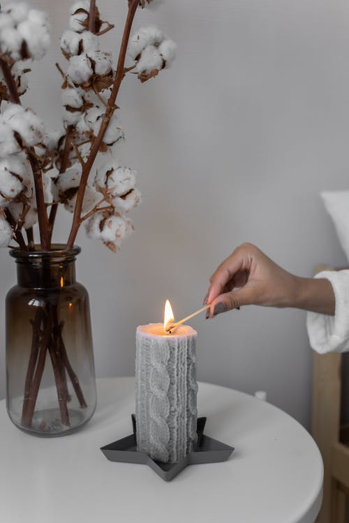 Close-Up Shot of a Person Lighting a Candle