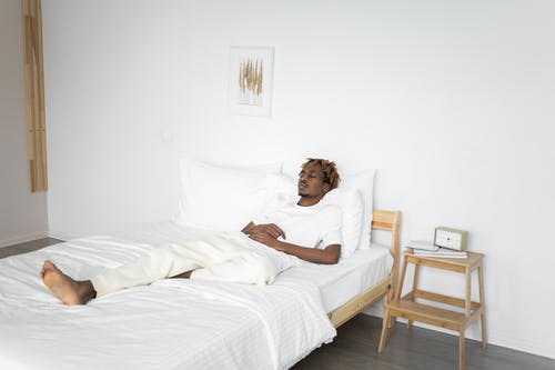 Woman in White Tank Top Lying on Bed