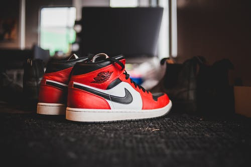 Pair of stylish red sneakers placed on floor with black carpet in room in daytime