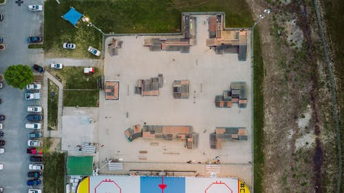 Aerial view of skate park with various funboxes and ramps near inline hockey rink located in town near road with parked cars