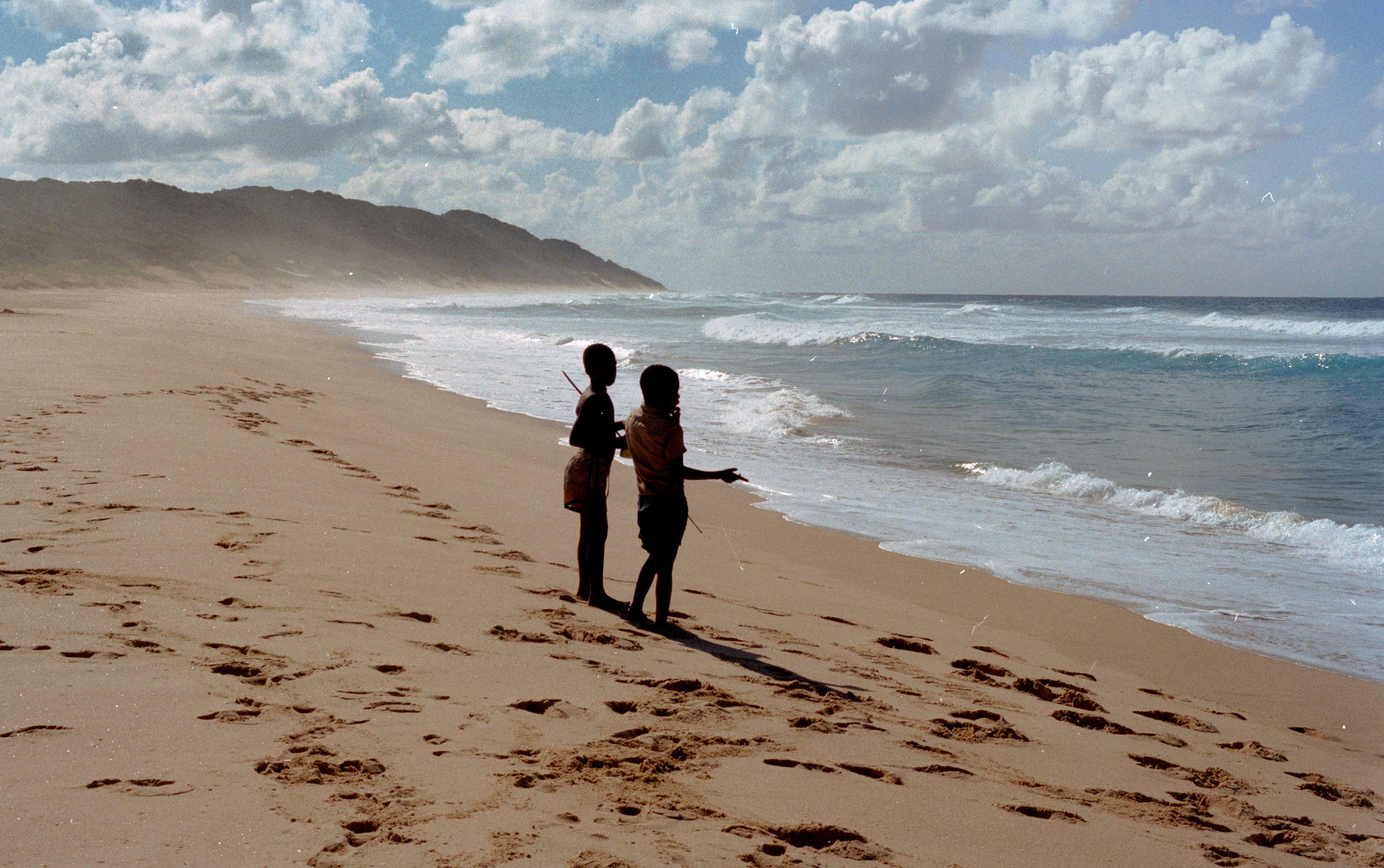 Two Children Stands on Shore Near Ocean at Daytime