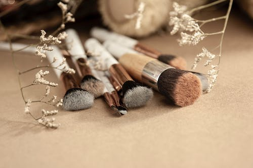 Bunch of professional makeup brushes for different beauty products spread out on beige surface near dried white flowers