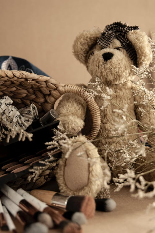Teddy bear placed near wicker basket with different beauty products and set of professional brushes on beige background