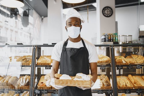A Baker Holding a Tray with Baked Goods
