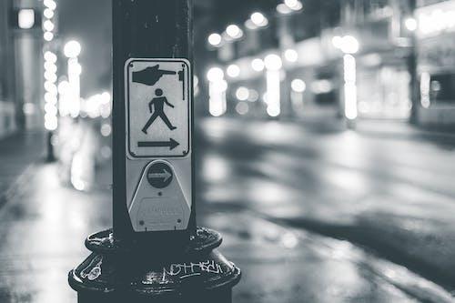 Pedestrian crosswalk button placed near roadway in city in evening time
