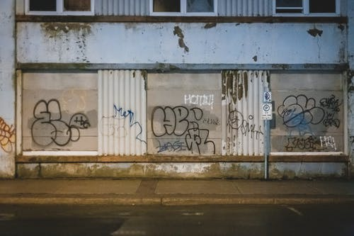 Graffiti on wall of aged building in evening time