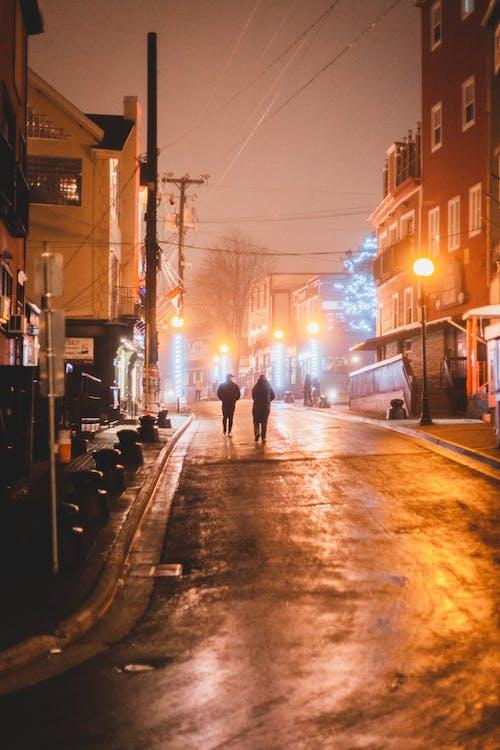 Unrecognizable people walking on wet asphalt road between residential buildings in city in evening time