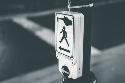 Black and white of pedestrian crosswalk call button placed on city street against asphalt road in evening time