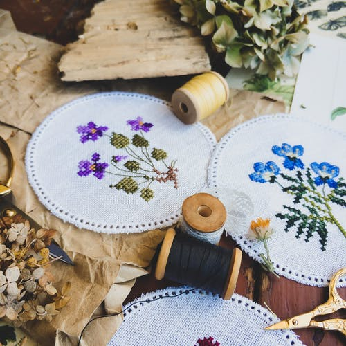 Various handmade cross stitch with threads and scissors