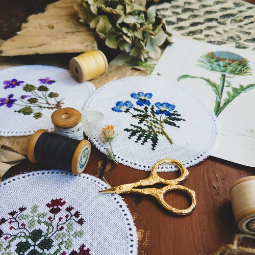 From above of assorted handmade embroidery made placed with threads and scissors for handicraft hobby