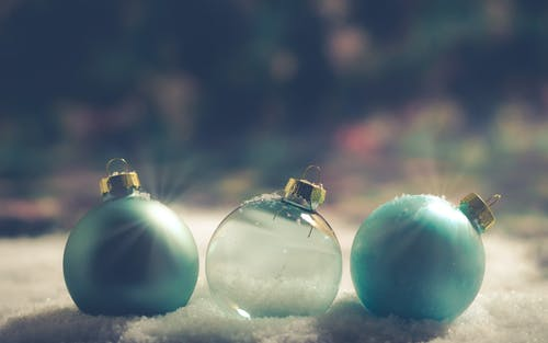 Two Green and Clear Baubles on snow