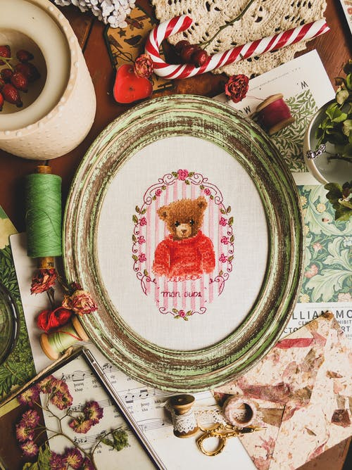 Oval frame with handmade cross stitch with threads