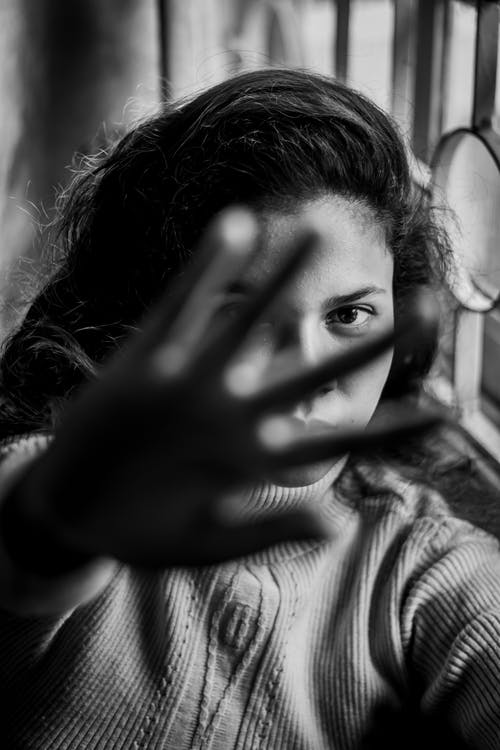 Grayscale Photo of Woman Covering Her Face With Her Hand