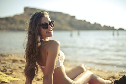 Woman in White Bikini Set Sitting Near Seashore