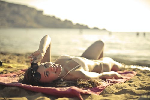 Woman Wearing Bikini Lying on Red Mat Near Seashore at Daytime