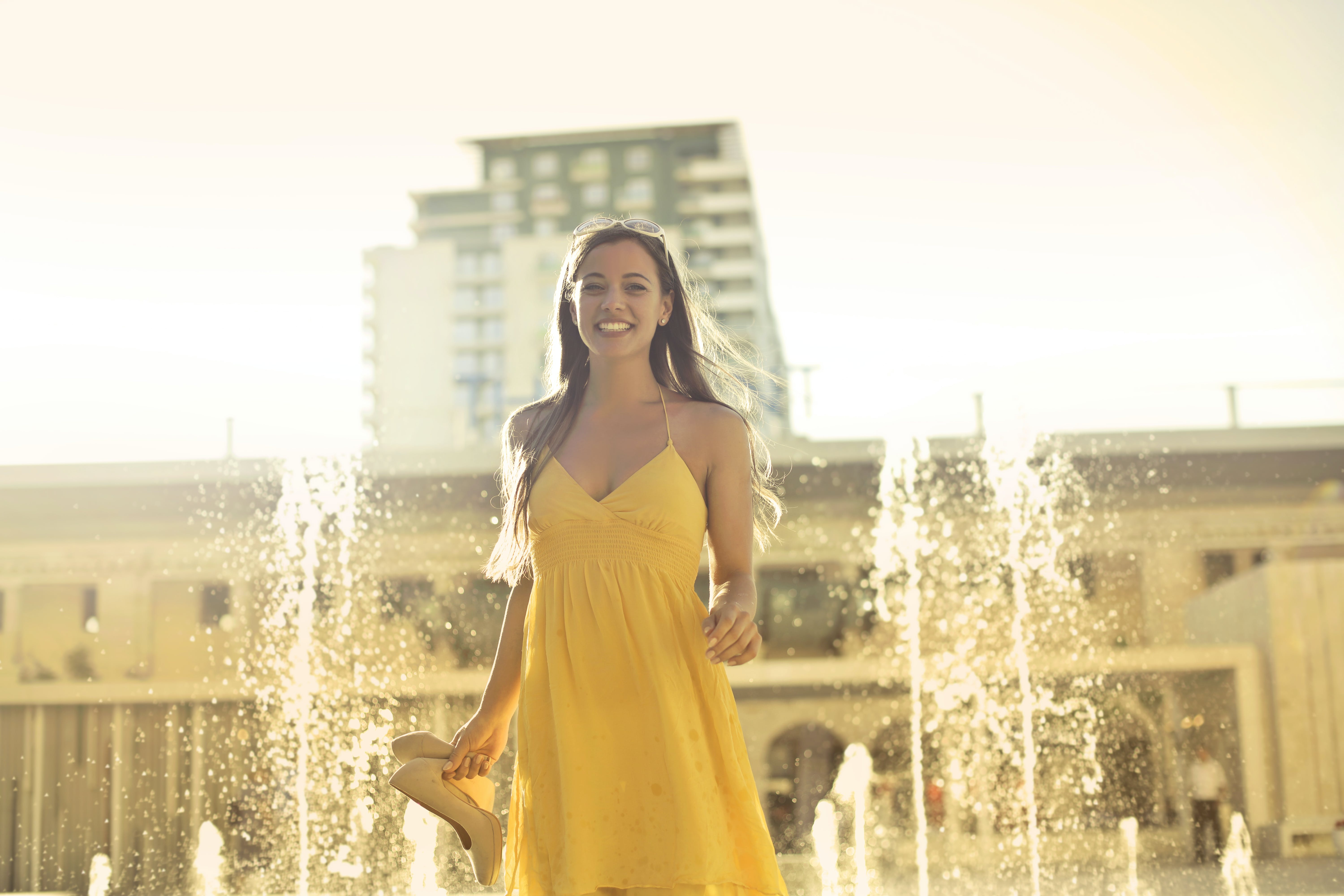 Woman Wears Yellow Spaghetti Strap Dress Stands Near Water Fountain