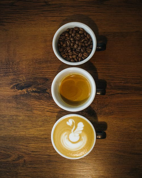 Top view arrangement of cups with fresh cappuccino espresso and coffee beans placed in row on wooden table
