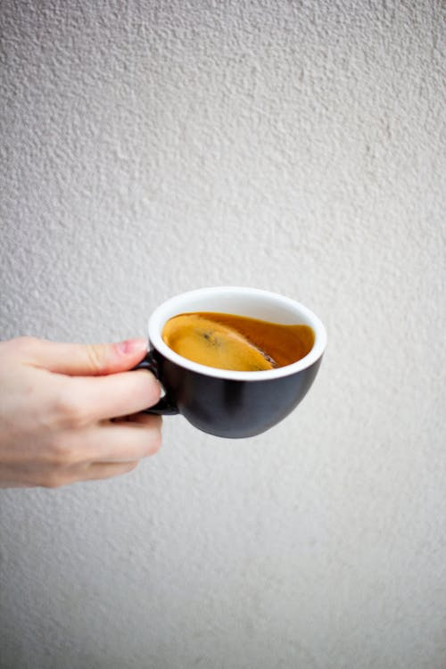 Crop unrecognizable person demonstrating cup of aromatic espresso