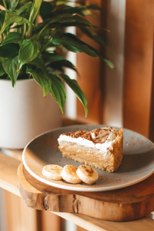 Delicious freshly baked cake on plate decorated with ripe banana and served on wooden shelf near lush houseplant