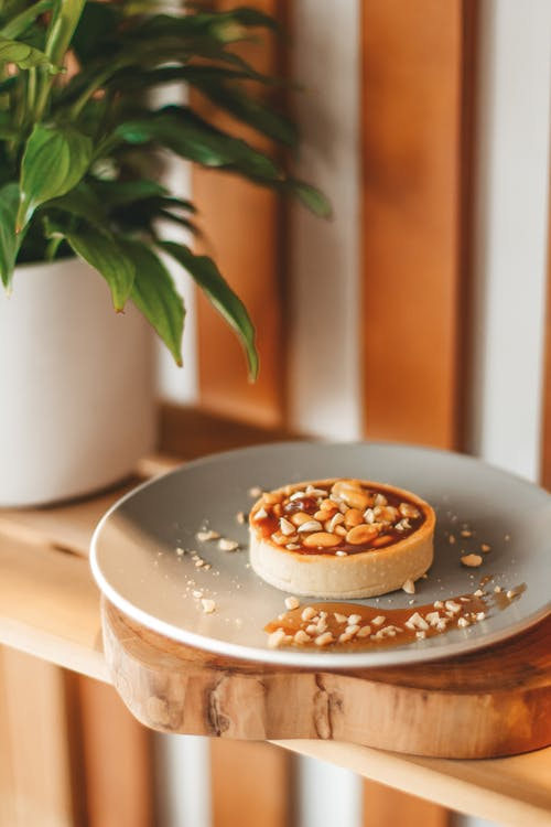 Delicious tart on plate served on wooden shelf