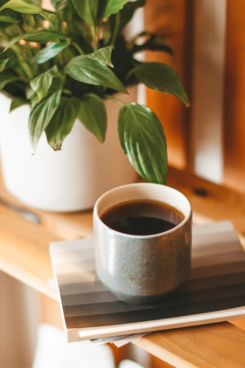 Cup of black coffee served on wooden shelf