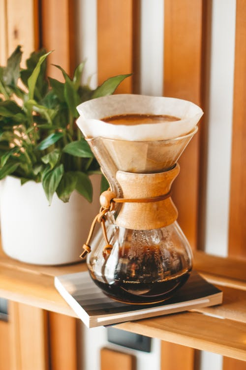 Aromatic delicious black coffee brewing in chemex and placed on wooden shelf near potted plant
