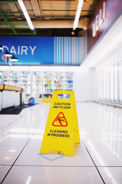 Yellow plastic warning sing with inscription Wet floor placed in empty store in modern mall