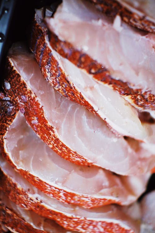 From above of tasty raw slices of fish placed in row in daylight