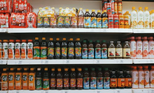 Shelves with various bottles of lemonades in supermarket