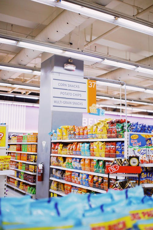 Area with corn snacks and potato chips in supermarket