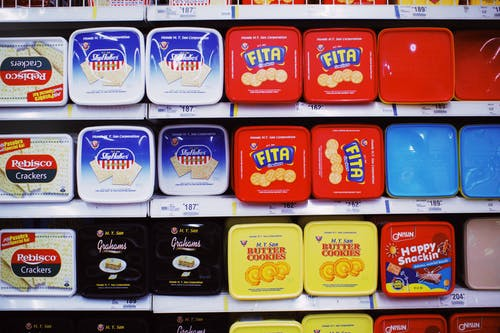Assorted colorful boxes of tasty sweet cookies placed on shelves with prices in supermarket