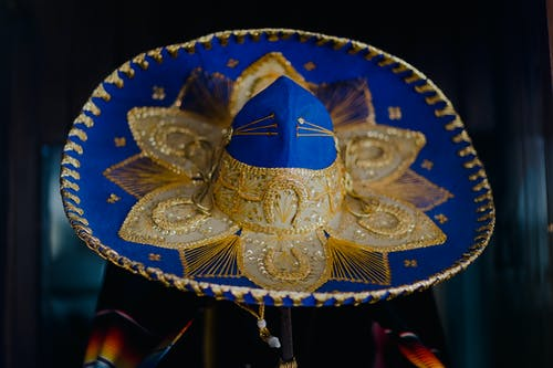 Blue and Gold Hat on Brown Wooden Table