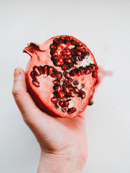 Person Holding Red Round Fruit