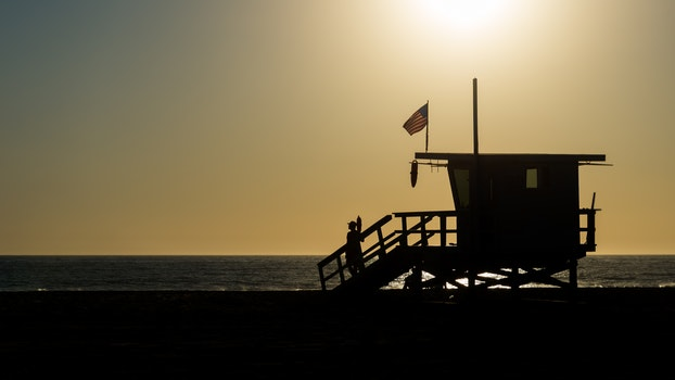 Silhouette of Life Guard House Near Ocean during Sunset