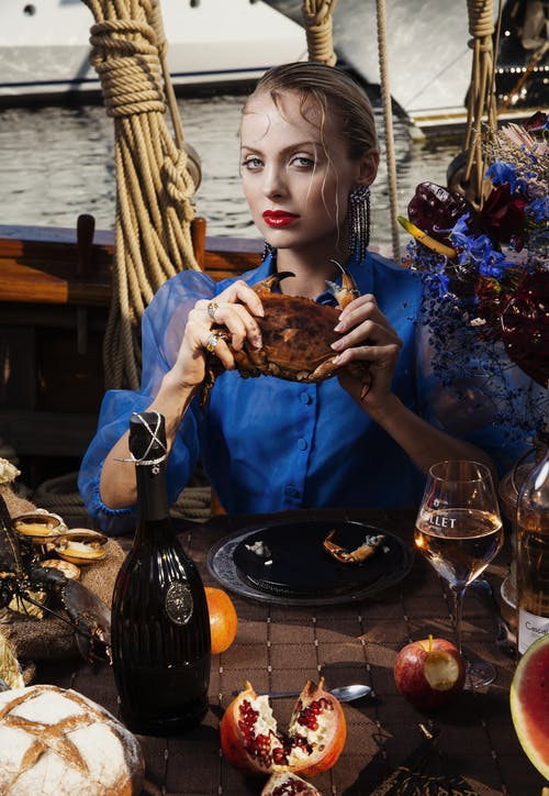 Attractive female looking at camera while sitting at table with tasty assorted food and wine during cruise on wooden vessel