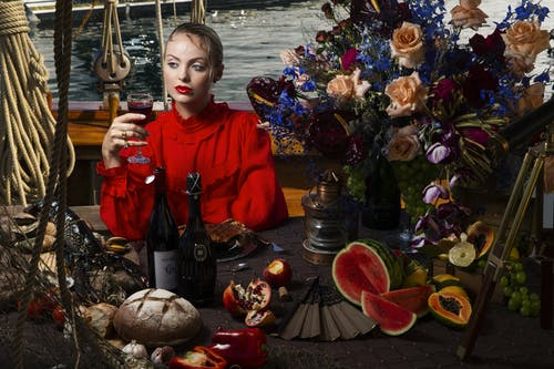 Serious female with wineglass of alcohol drink in stylish clothes looking away while sitting at table with assorted food on ship