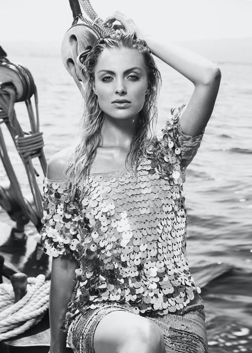 Black and white of charming female in trendy outfit looking at camera while sitting on yacht near rippling sea during trip
