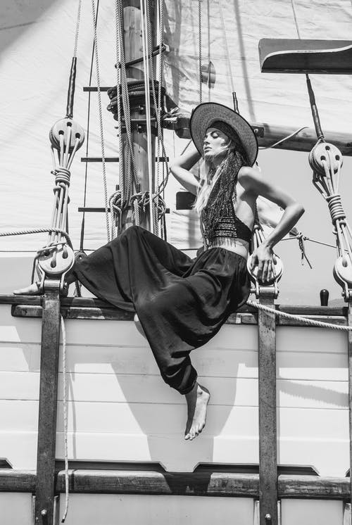 Black and white full body side view of stylish female in hat sitting on wooden ship during cruise on summer day