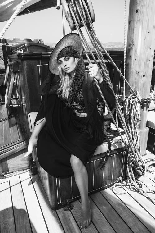 Black and white full body of trendy barefoot female in hat looking at camera while sitting on deck of ship during trip