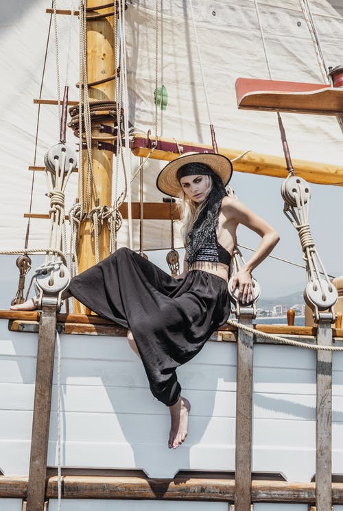 Trendy woman sitting on wooden ship