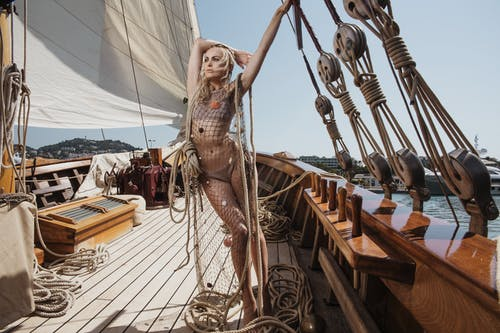 Full body of charming female wearing swimsuit and mesh cover up standing on wooden deck of yacht during summer trip