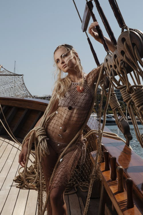 Charming female wearing swimwear and mesh cover up with ropes standing on wooden deck of yacht during cruise on summer day