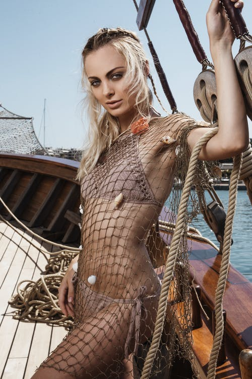 Attractive female in swimwear and mesh cover up looking at camera while standing on wooden yacht during trip on summer day