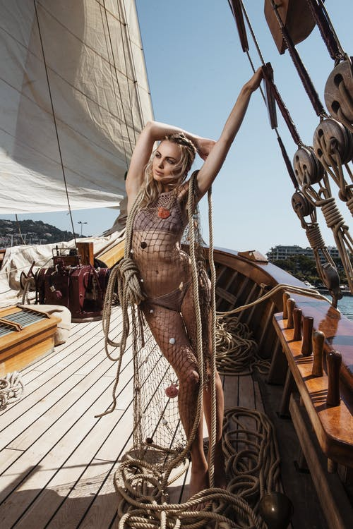Full body of gorgeous female in swimsuit standing on wooden deck of yacht with ropes during cruise on summer day