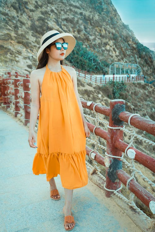 Woman in Orange Sleeveless Dress Standing on Concrete Stairs