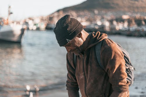 Man in Brown Jacket and Black Knit Cap Standing Near Body of Water
